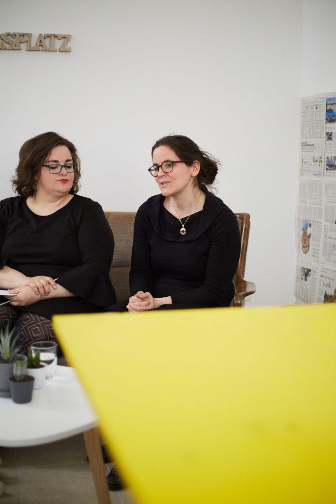 zwei Frauen in schwarzen Kleidern, Sara und ich, sitzen auf einem Sofa vor einem gelben Tisch und überlegen/ sprechen miteinander