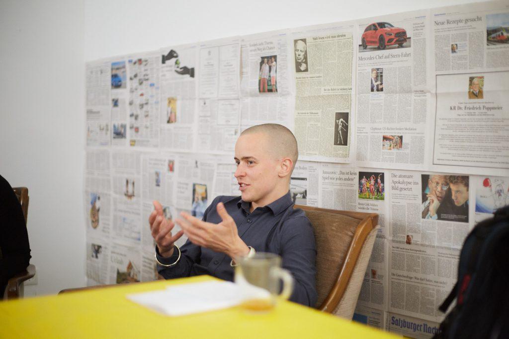 ein jüngere Mann mit einem grauen Hemd sitzt auf einem braunen Sessel und so spricht ggerade und gestikuliert dabei mit seinen Händen